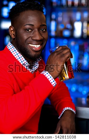 Young african guy drinking beer in nightclub - stock photo