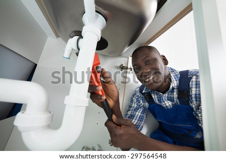 Young African Handyman Repairing Sink Pipe With Worktool - stock photo