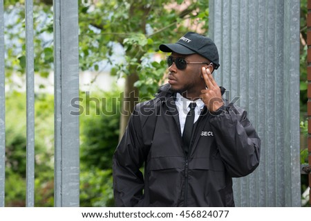 Young African Male Security Guard Listening To Earpiece
