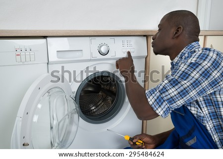 Young African Male Technician Pressing Button On Washing Machine - stock photo