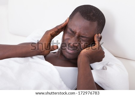 Young African Man Having Headache Lying On Bed