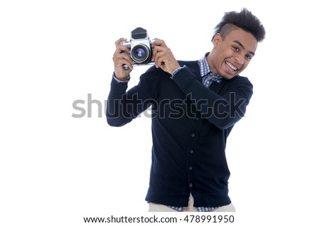 Young african man holding an old camera and being happy on the pictures taken.