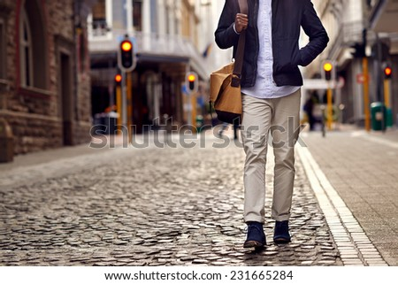 Young african man on vacation exploring european city cobblestone street - stock photo