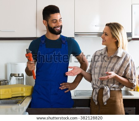 Young African plumber and happy white housewife inside