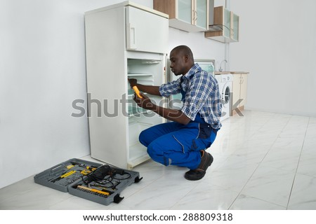 Young African Repairman Repairing Refrigerator In Kitchen Room