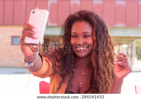 Young african student making a pause to take a selfie - stock photo