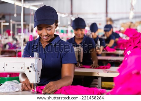 young african textile worker sewing on production line - stock photo