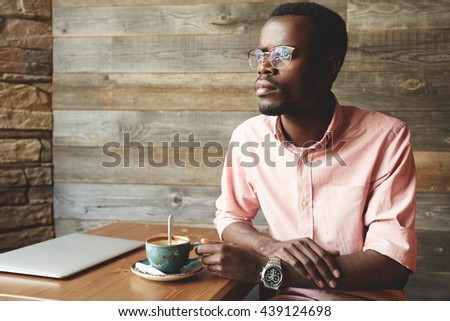 Young African wearing pink shirt and glasses, sitting at the cafe table with a cup of coffee, remembering his student life, while waiting for his university mate, against the wooden background - stock photo