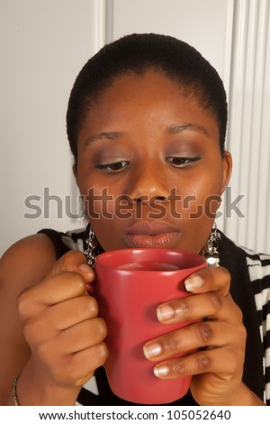 Young african woman blowing on her hot coffee cup - stock photo