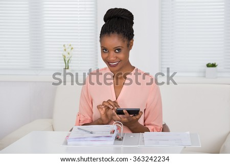 Young African Woman Calculating Invoice With Calculator - stock photo