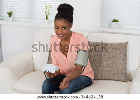 Young African Woman Checking Blood Pressure At Home - stock photo