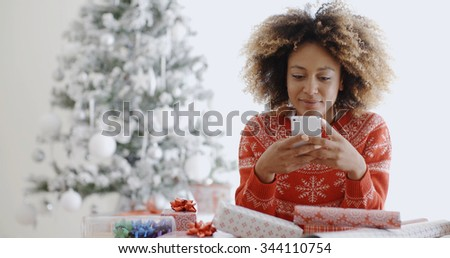 Young African woman checking for Xmas messages on her mobile phone as she sits wrapping gifts in front of the Christmas tree - stock photo