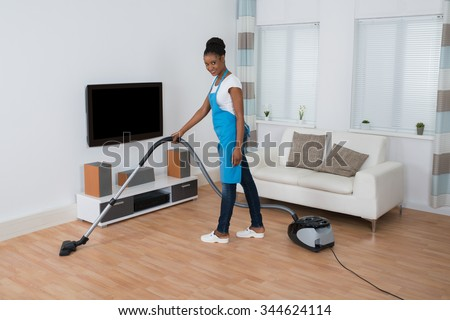Young African Woman Cleaning Hardwood Floor With Vacuum Cleaner - stock photo