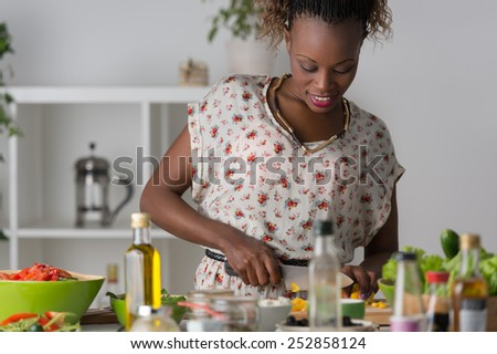 Young African Woman Cooking. Healthy Food - Vegetable Salad. Diet. Dieting Concept. Healthy Lifestyle. Cooking At Home. Prepare Food - stock photo