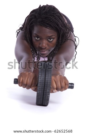 young african woman doing some push-ups with a exercise wheel (isolated on white) - stock photo