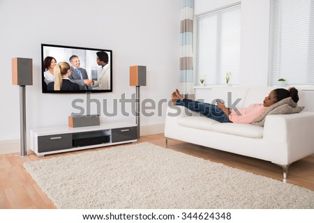 Young African Woman Falling Asleep While Watching Television At Home - stock photo