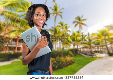 Young african woman holding grey laptop