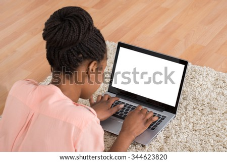 Young African Woman Lying On Carpet Using Laptop - stock photo