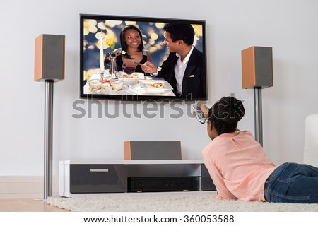 Young African Woman Lying On Carpet Watching Television