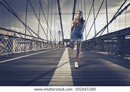 Young african woman running on Brooklyn Bridge