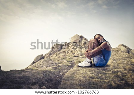 Young african woman sitting on a rock