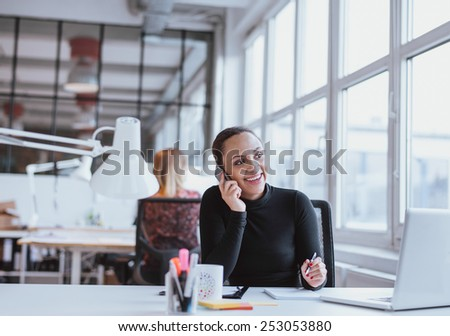 Young african woman using mobile phone while at work. Female executive in conversation on a mobile phone while sitting at her desk. - stock photo
