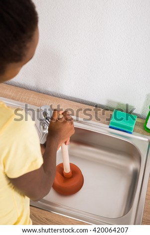 Captivating Young African Woman Using Plunger In Kitchen Sink