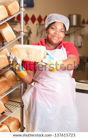 young african woman wearing heat-protected gloves preparing fresh bread loaves to be cooled on the rack