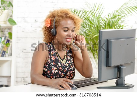 young African woman with a headset and computer