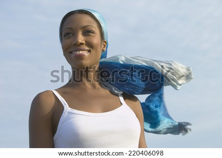 Young African woman with head scarf blowing in the wind - stock photo