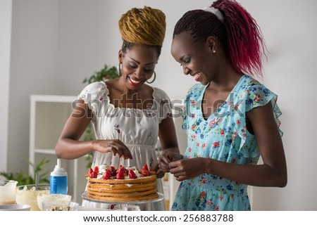 Young african women at the kitchen cooking cake with strawberry - stock photo