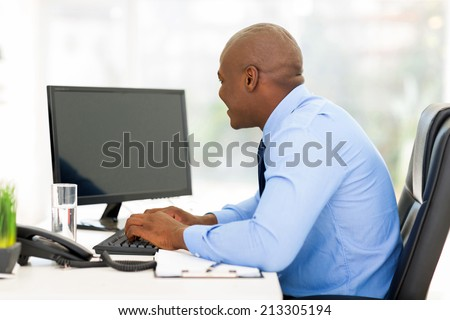 young afro american businessman working on a computer in modern office - stock photo