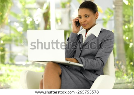 Young Afro American Businesswoman using laptop on knees and giving a call with mobile phone - stock photo