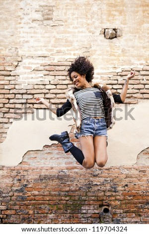 Young afro american girl jumping in urban background - stock photo