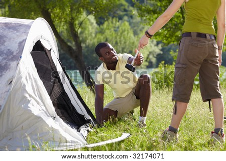 Young afro-american man fastening tent and holding hammer
