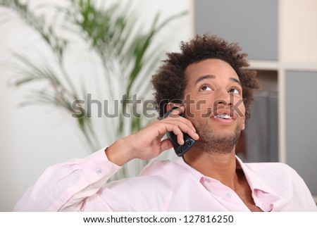 young Afro-American talking on his cell at home - stock photo