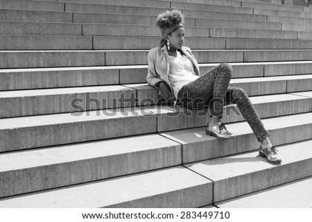 young afro american woman sitting on stairs - black and white photography - stock photo