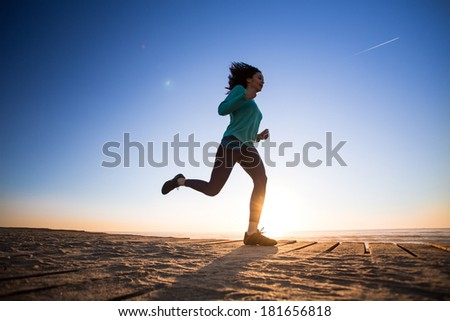 Young afro woman running on the beach - stock photo