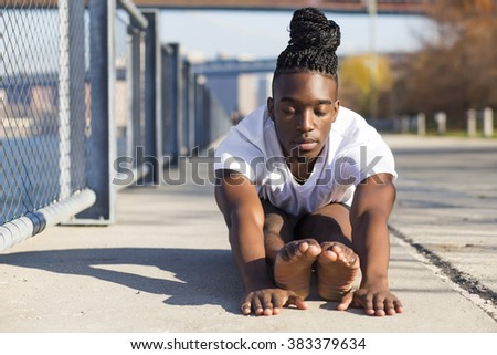 Young afroamerican man practicing yoga outdoors, in New York city.