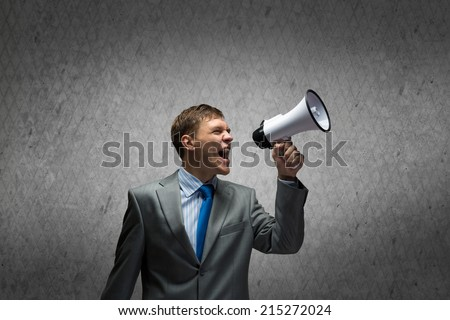 Young aggressive businessman screaming furiously in megaphone - stock photo