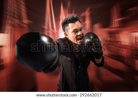 young aggressive businessman training shadow boxing at gym with gloves throwing vicious punch in angry rage face expression, fighting business concept, motion blur background.