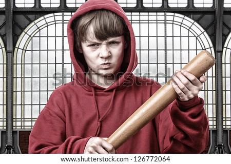 Young aggressive teenage boy with a baseball bat - stock photo