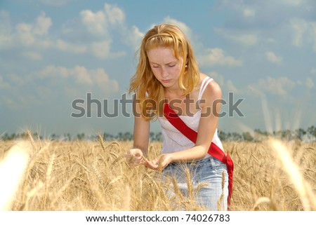 Young agronomist examines the maturity of the wheat harvest - stock photo