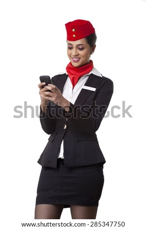 Young airhostess text messaging on cell phone isolated over white background