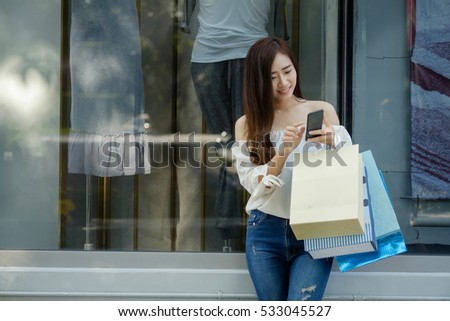 young aisin woman using her smartphone and carry bag while doing some shopping in a mall