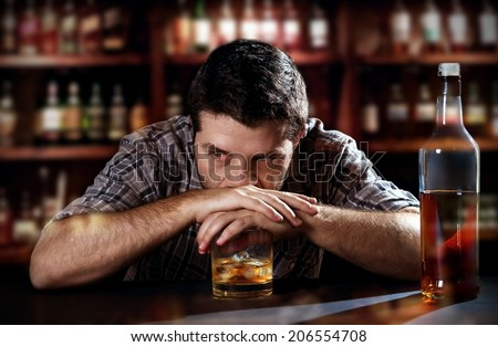 young alcoholic drunk man thoughtful about alcohol addiction drinking indoors at bar of an irish pub leaning hands on whiskey glass in alcoholism concept - stock photo