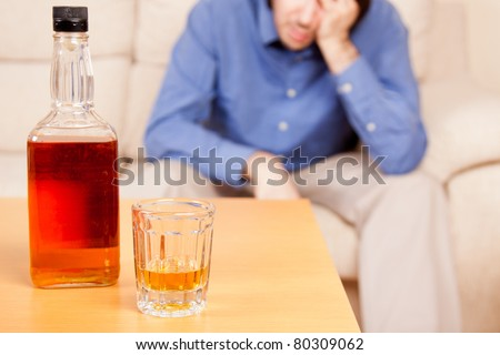 Young alcoholic man drinking whisky in his home. - stock photo