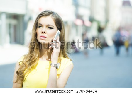 Young alluring beautiful lady with bright makeup and curly hair standing in street speaking on phone on city background, horizontal picture