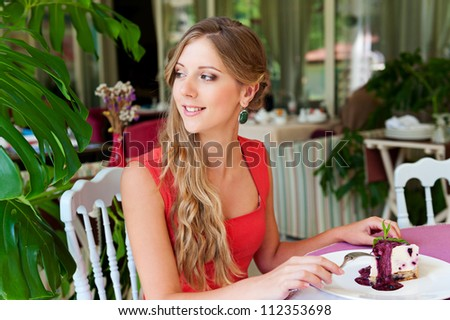 young alluring woman resting in the cafe and eating cake - stock photo