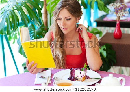 young alluring woman with book sitting in cafe - stock photo